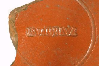 Part of a Decorated Samian ware Bowl with stamp inside.