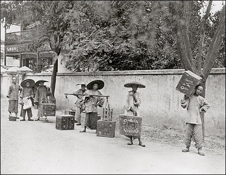 Porters lugging tea chests on carrying poles to the shipper.